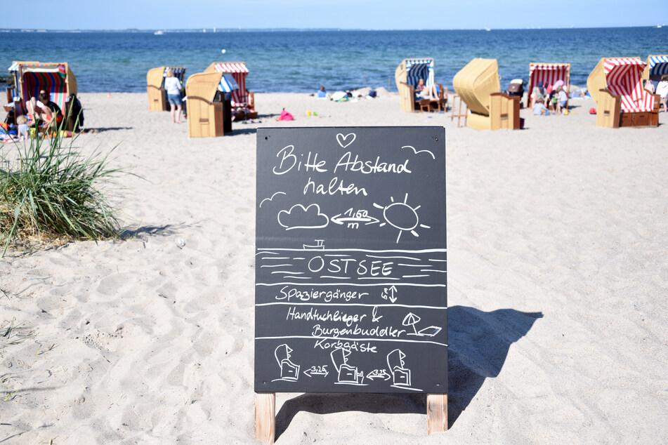 """Ein Schild mit der Aufschrift """"Bitte Abstand halten"""" steht am Zugang zum Strand an der Ostsee."""