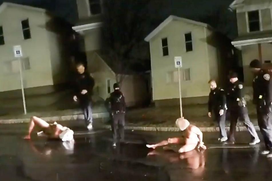 """Daniel Prude liegt auf der Straße, nackt. Die Polizisten stehen um ihn herum, nachdem sie ihm einen """"Spuckschutz"""" aufgezogen haben."""