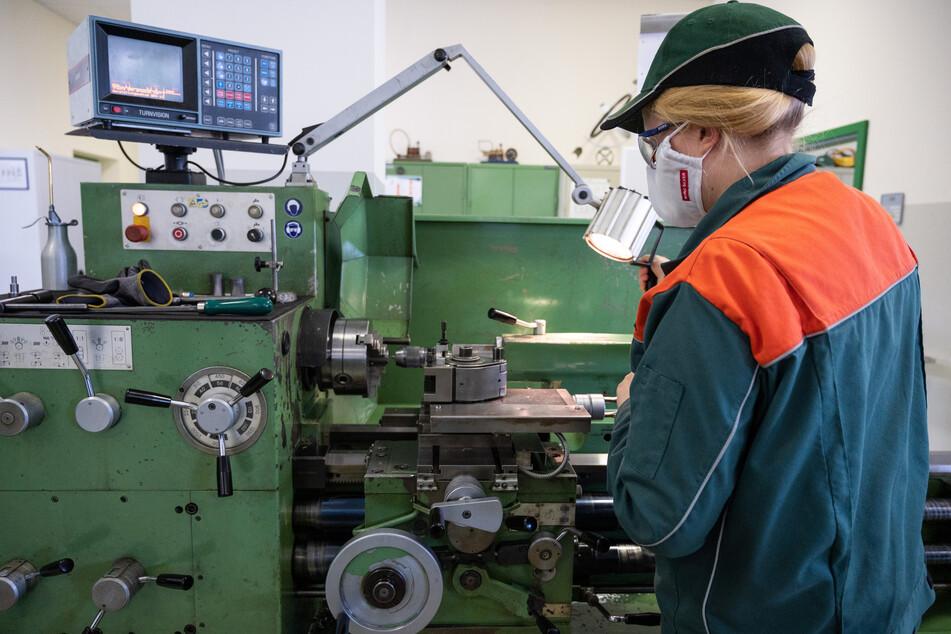 Eine Auszubildende trägt einen Nasen-Mundschutz bei der Arbeit an einer Drehbank in einer Ausbildungswerkstatt. (Archivbild)