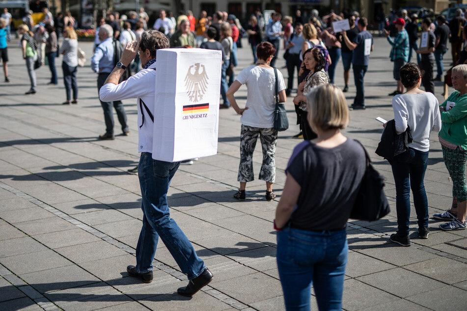 """""""Grundgesetz"""" steht auf einem Schild an dem Rücken eines Teilnehmers einer Demonstration gegen die Einschränkungen der Grundrechte in Zeiten der Corona-Krise."""