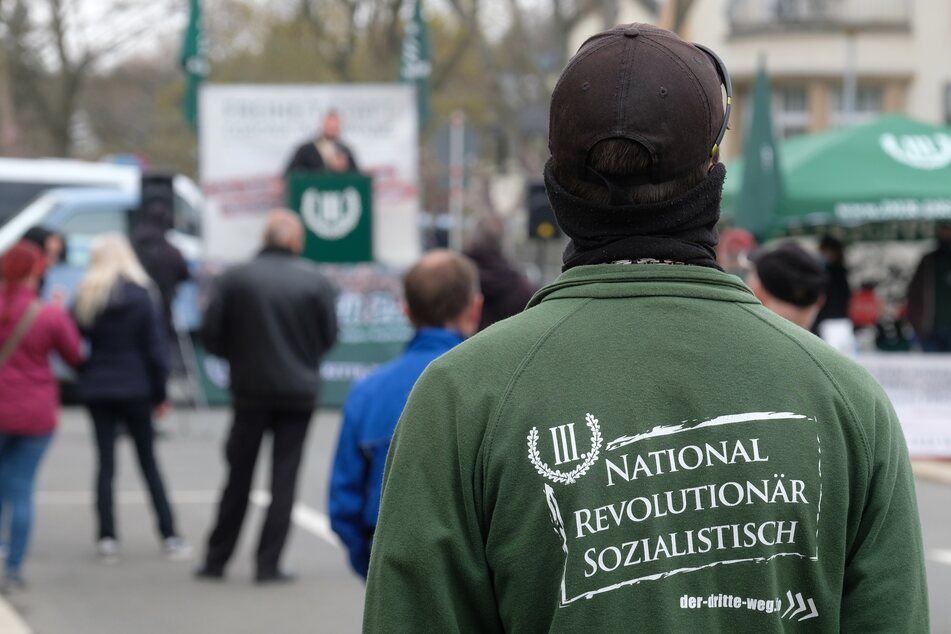 """Ein Teilnehmer einer Kundgebung der rechtsextremen Partei """"Der III. Weg"""" trägt eine Jacke mit der Aufschrift """"National revolutionär sozialistisch""""."""