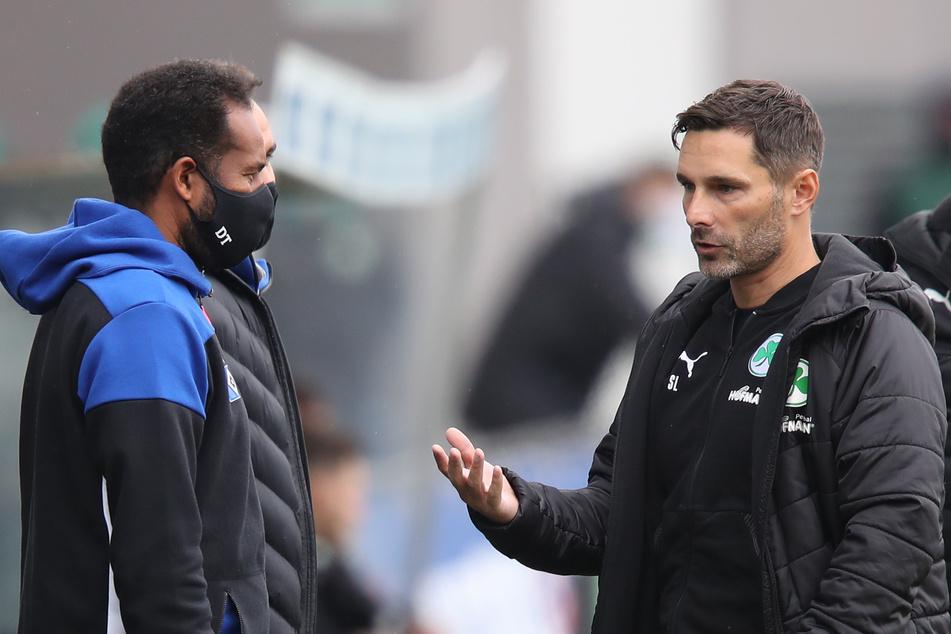 HSV-Coach Daniel Thioune (l) und der Fürther Trainer Stefan Leitl (r) unterhalten sich vor Spielbeginn.