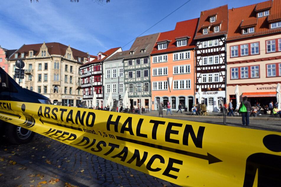 """Thüringen, Erfurt: """"Abstand halten!"""" in deutscher und englischer Sprache steht auf einem Flatterband am Domplatz inmitten der Altstadt"""