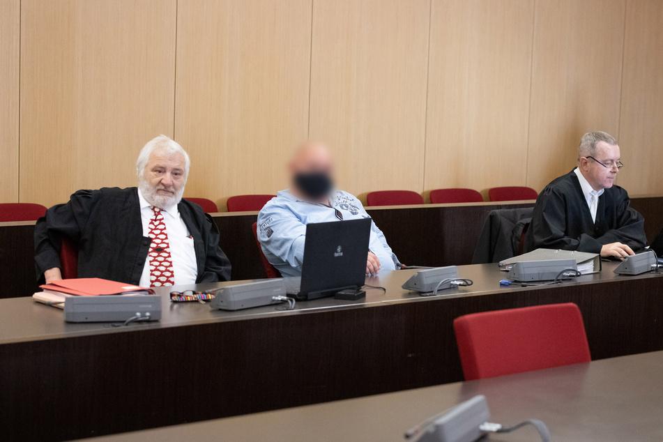 Der Angeklagte (M) sitzt zwischen seinen Anwälten in einem Saal des Düsseldorfer Landgerichts.