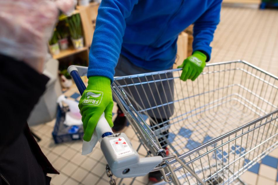 """Dresden: Ein Mitarbeiter des Sicherheitsdienstes eines """"Konsum""""-Supermarkts trägt Schutzhandschuhe, während er den Griff eines Einkaufswagens eines Kunden vor dem Besuch des Marktes mit einem Desinfektionstuch abwischt."""