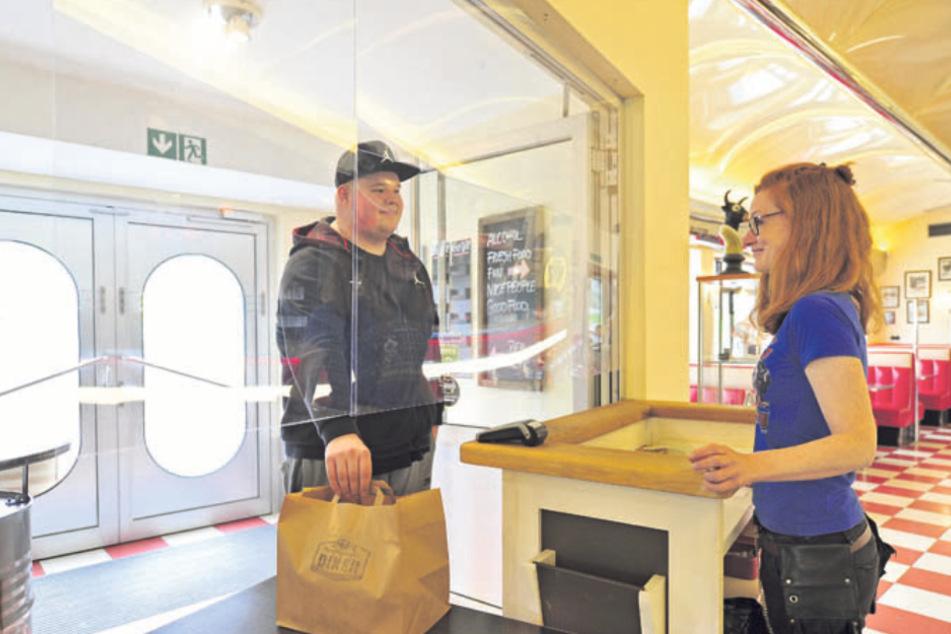 Stammkunde Oliver Reinert (25) erhält seine Bestellung von Mr. Meyers Diner -Mitarbeiterin Anja Schmidt (37) durch eine Plexiglasscheibe.