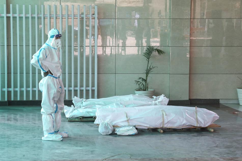 Neu Delhi: Ein Angehöriger steht in einem Krematorium in Schutzkleidung vor dem Leichnam eines verstorbenen Corona-Patienten.