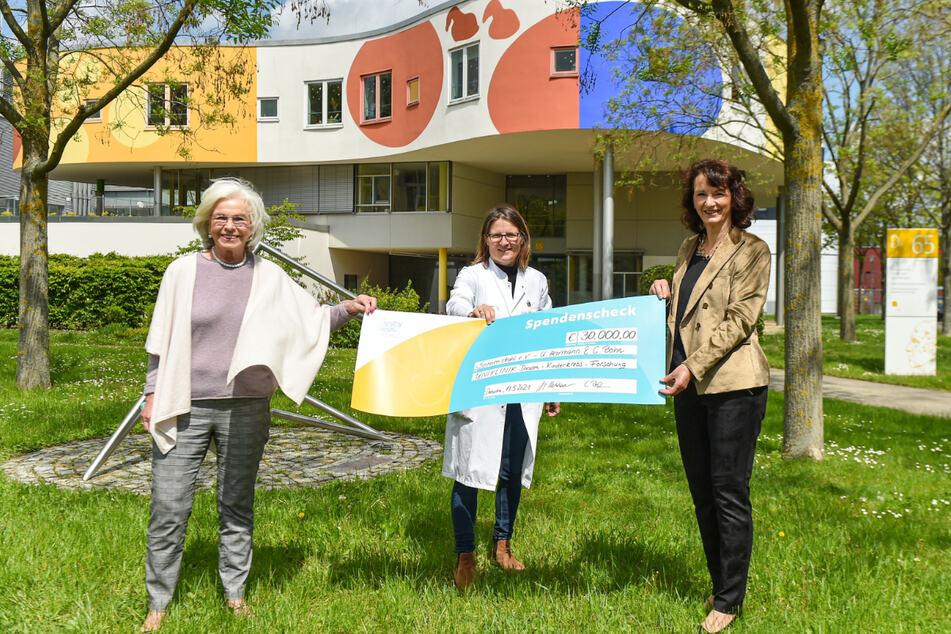 Ursula Herrmann (l.) und Cornelia Bohn (r.) übergeben die Spende an Julia Hauer vom Universitätsklinikum.