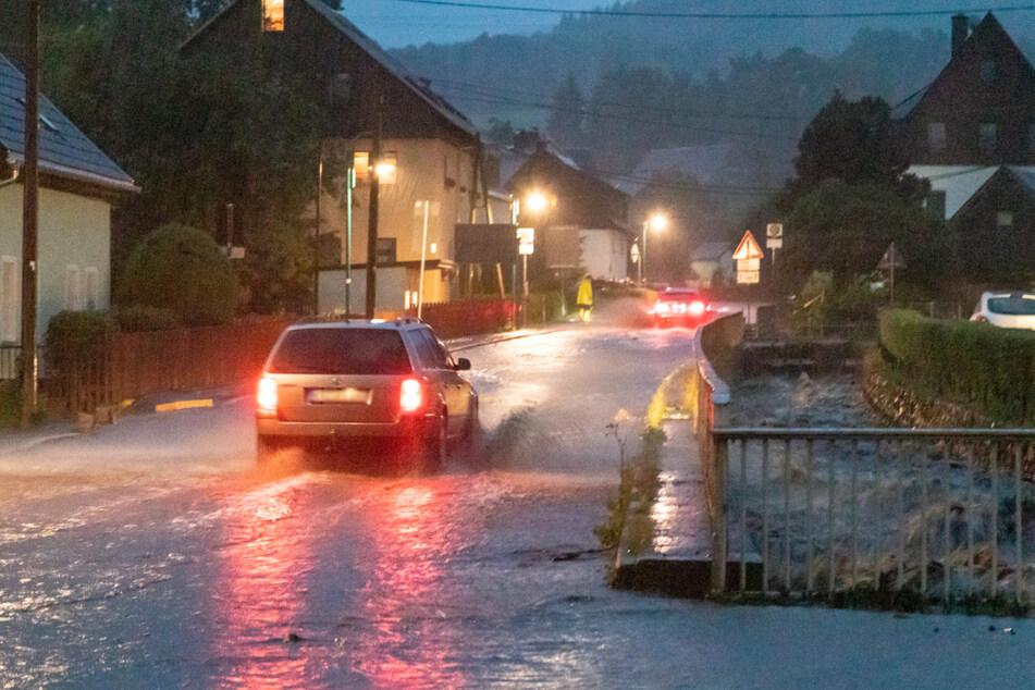 Ein Auto kämpft sich in Jöhstadt über eine überflutete Straße. Neben der Fahrbahn tobt der Steinbach.