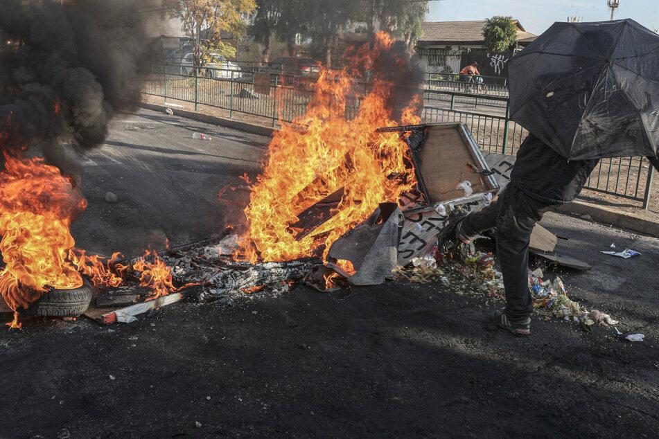 """euer brennt nach einem Protest von Anwohnern des Vororts """"Cerrillos"""" inmitten der Corona-Pandemie. Eine Gruppe randalierte, weil die Nachbarschaft keine Lebensmittelkisten von der Regierung erhalten hatte."""