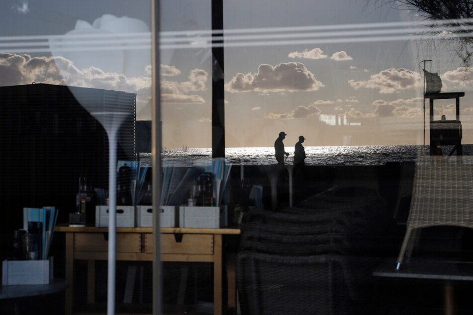 Palma: Menschen spiegeln sich im Fenster einer geschlossenen Bar in der Schinkenstraße.