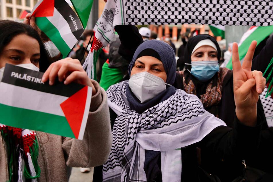 Teilnehmer an einer pro-palästinensischen Demonstration schwenken am Samstag die Landesflaggen am Potsdamer Platz.