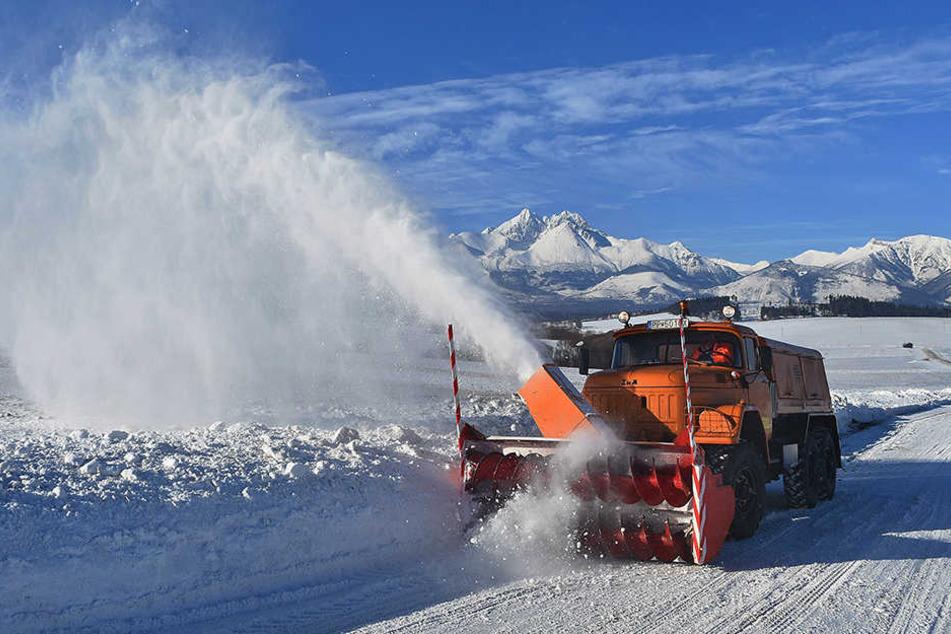 Ein Schneepflug räumt am Freitag die schneebedeckte Straße bei Strane im slowakischen Teil der Tatra.