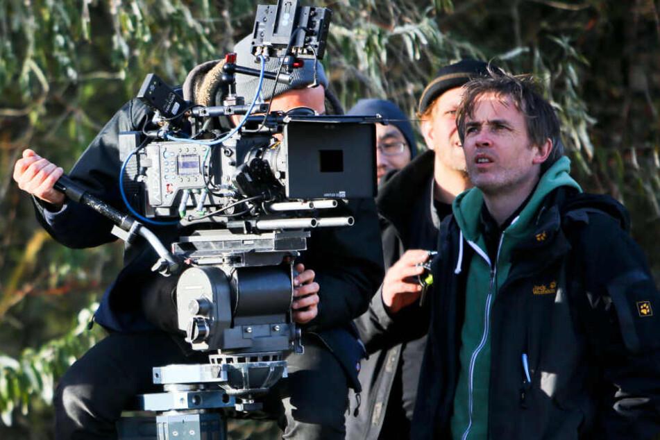 """Regisseur Eoin Moore (rechts) blickt bei TV-Dreharbeiten für """"Polizeiruf 110"""" am Strand von Markgrafenheide (Mecklenburg-Vorpommern) auf den Monitor der Filmkamera."""
