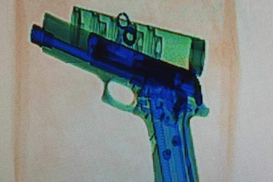 Das Foto zeigt eine Roentgenaufnahme einer Pistole in einem Postpaket.