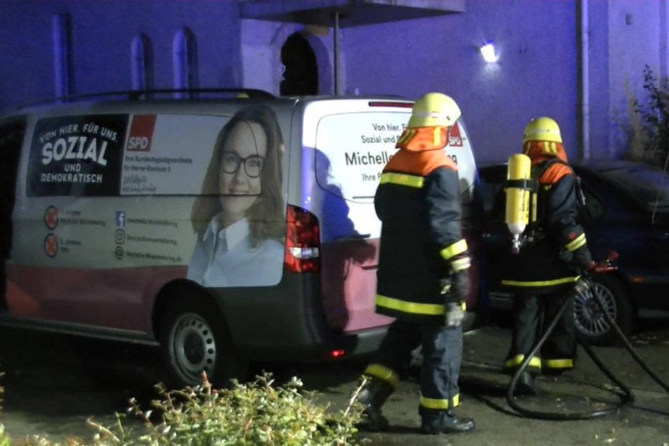 Feuerwehrleute stehen neben dem Lieferwagen, der Opfer des Brandanschlags wurde.