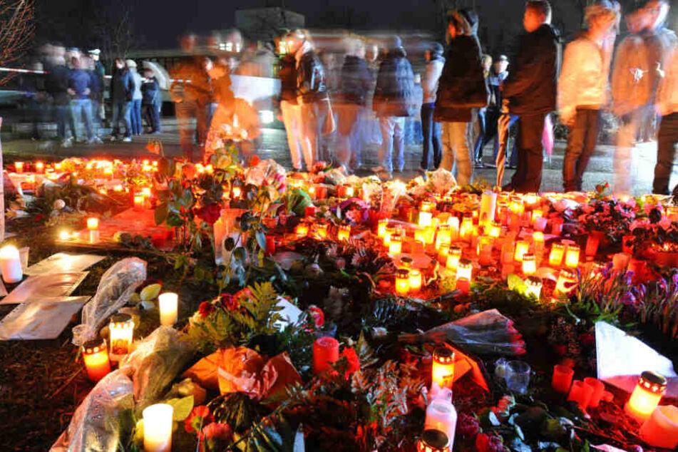 Trauernde stehen am 12.3.2009 vor einem Meer aus Grablichtern und Blumen.