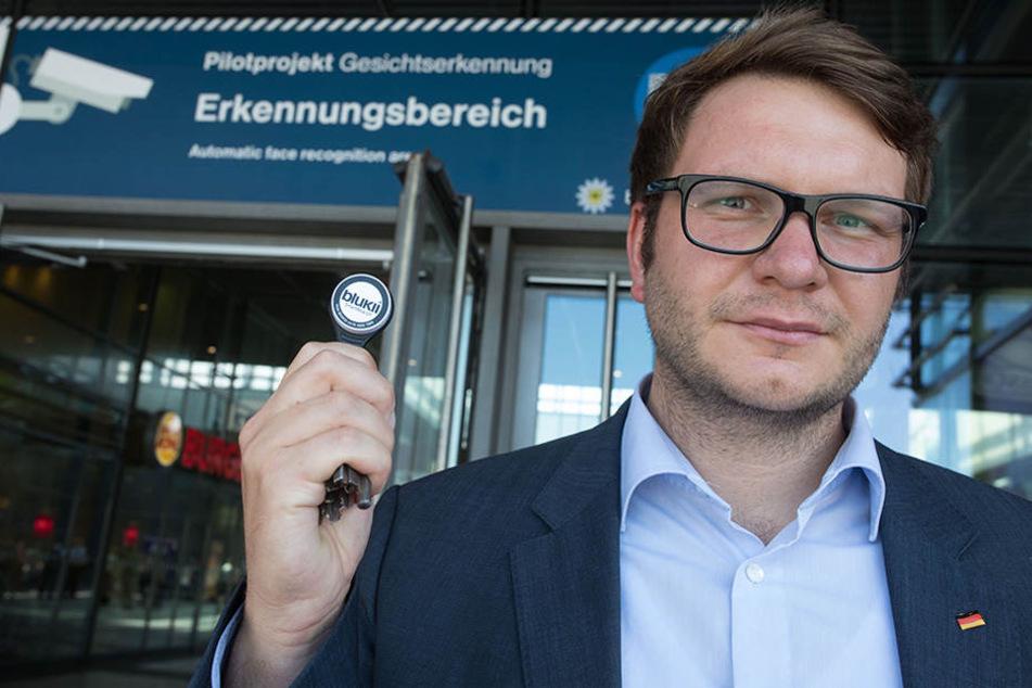 Der Bundestagsabgeordnete Marian Wendt (CDU) präsentiert anlässlich des Starts der Gesichtserkennung einen Sender, der von den Testpersonen getragen wird.