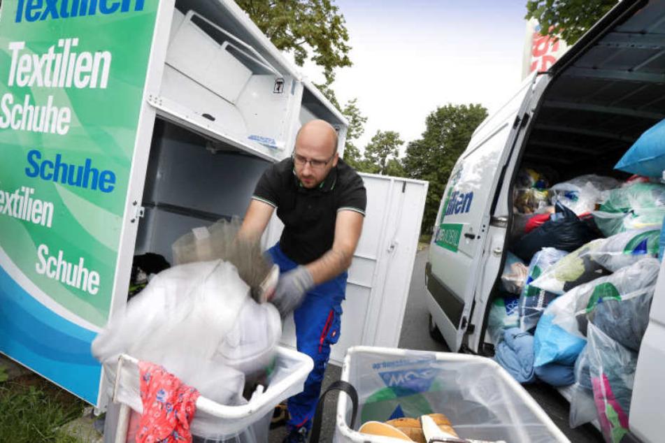 Ein Mitarbeiter holt die von den Dieben zurückgelassenen Kleider am Container am Real-Markt ab.