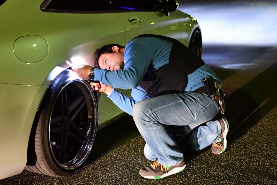 Gemeinsam kontrollieren die Beamten die aufgemotzten Autos. (Archivbild)