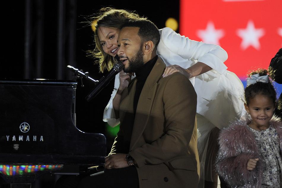 John Legend (41) am Piano wird von seiner Frau Chrissy Teigen (34) umarmt. Daneben steht die kleine Luna (4).