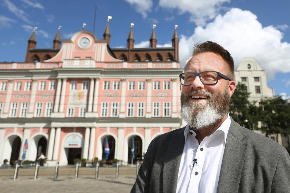 Rostocks Oberbürgermeister Claus Ruhe Madsen (parteilos) steht gut gelaunt vor dem Rathaus.