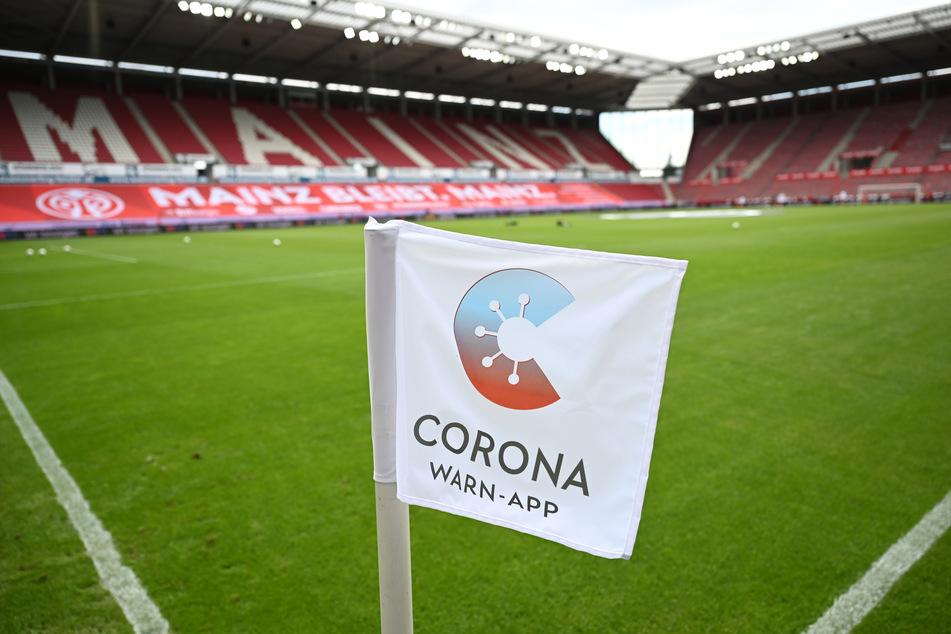 Eine Eckflagge mit dem Logo der deutschen Corona-Warn-App steht am Spielfeldrand des Mainzer Stadions.
