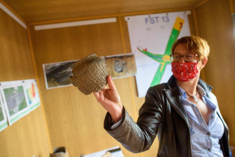 Susanne Friederich, Abteilungsleiterin Bodendenkmalpflege vom Landesamt für Denkmalpflege und Archäologie Sachsen-Anhalt, zeigt eine 3000 Jahre alte Keramik mit Fingernageleindrücken, die an der Grabungsfläche gefunden worden ist.
