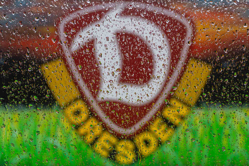 Das Logo des Fußball-Zweitligisten SG Dynamo Dresden ist hinter Regentropfen an einer Autoscheibe zu sehen. Allen Spielern aus Dresden wurde eine 14-tägige häusliche Quarantäne verordnet, da zwei von ihnen positiv auf das Coronavirus getestet wurden.