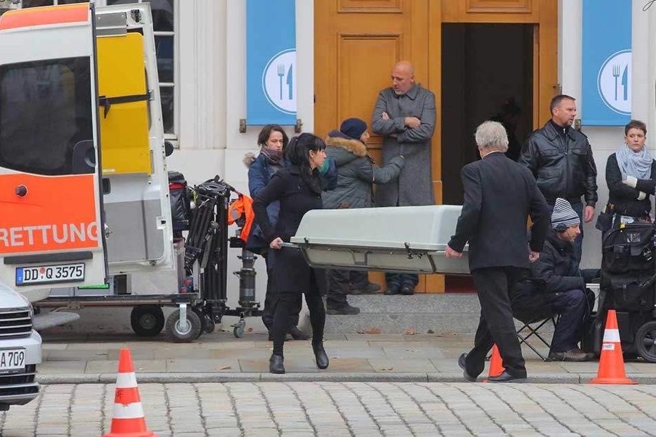 Der tote Wirt wird in einem Sarg abtransportiert.