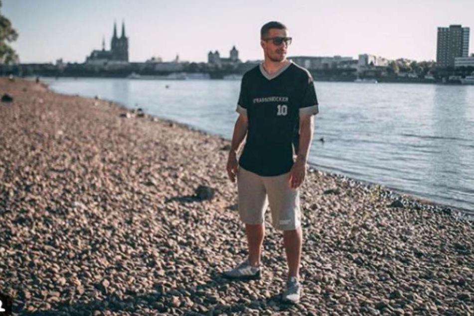 Hier steht Lukas Podolski am Rhein in Köln.