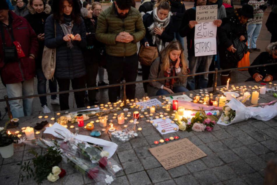 Entsetzen und Trauer nach dem Attentat. Menschen legen in Straßburg Kerzen nieder.