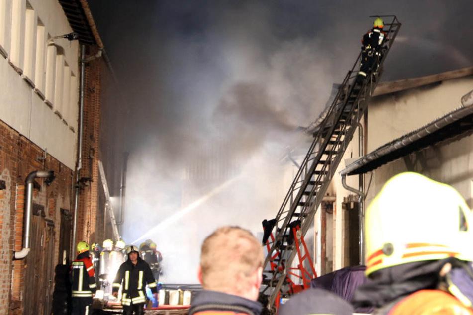 Lagerhalle mit Rennwagen steht in Flammen