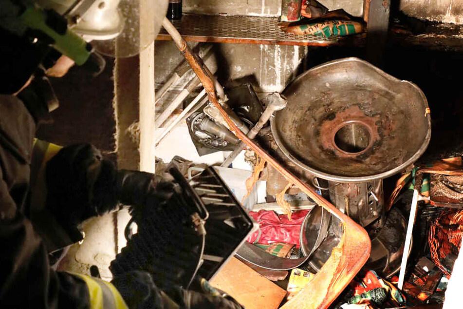 Ein Feuerwehrmann betrachtet durch den Brand beschädigte Gegenstände in der Gartenlaube.