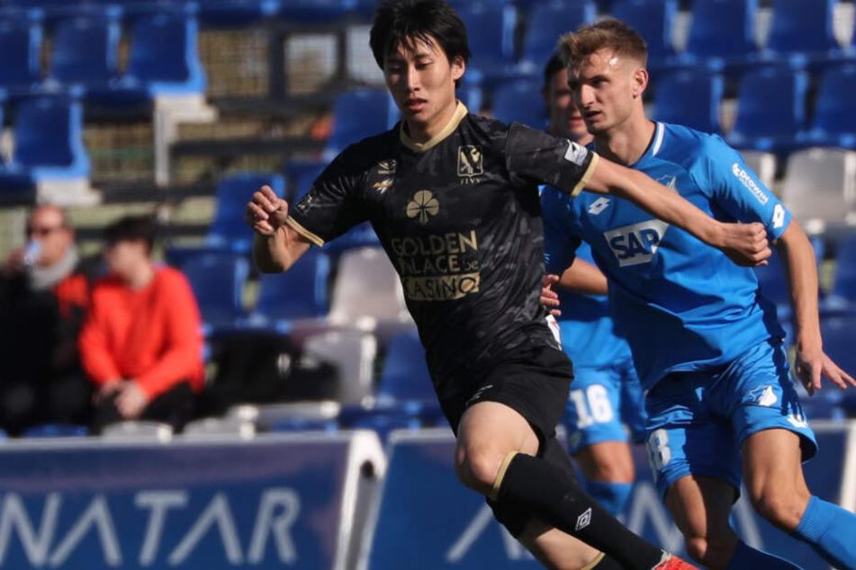 Daichi Kamada (22, links im Bild) kämpft in einem Testspiel für den belgischen Club VV St. Truiden gegen Hoffenheims Stefan Posch um den Ball.