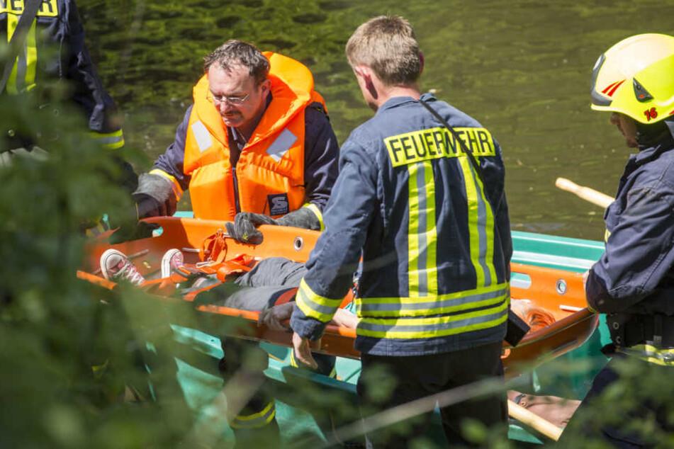 Feuerwehrleute sichern das improvisierte Rettungsboot, mit dem die junge Frau über die Zschopau gebracht wurde.