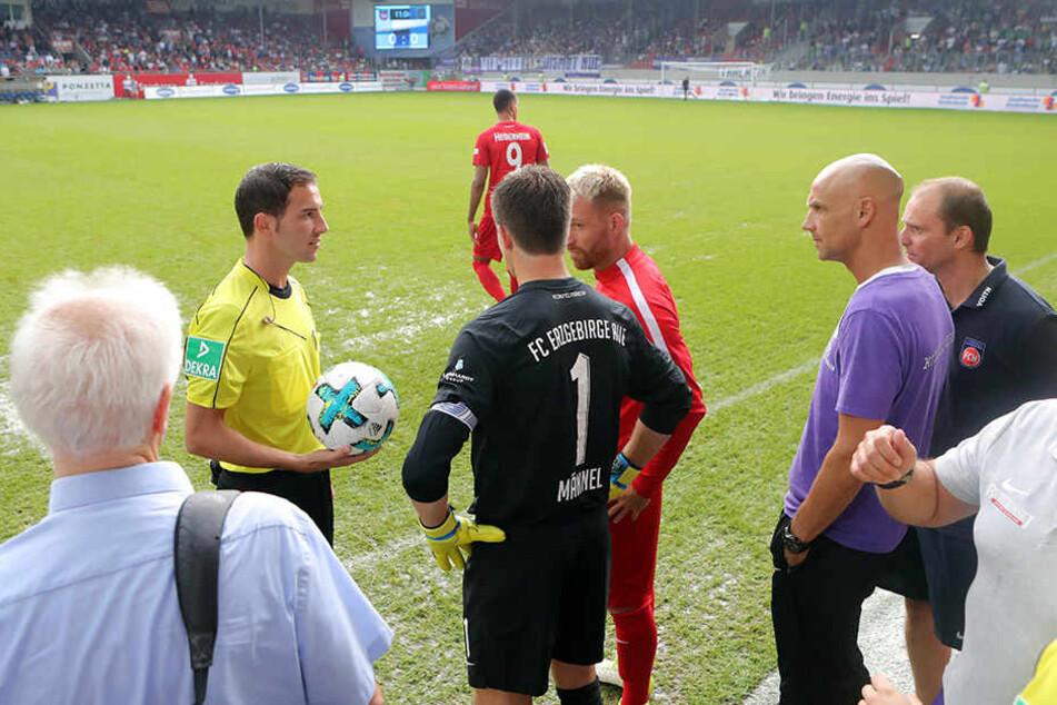 Schiedsrichter Benjamin Brand unterbricht die Partie und ruft die Kapitäne Martin Männel (schwarzes Trikot) und Marc Schnatterer (rechts daneben) zu sich.