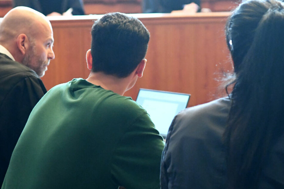 Der Angeklagte (Mitte) sitzt im Gerichtssaal zwischen seinem Anwalt und einer Dolmetscherin.
