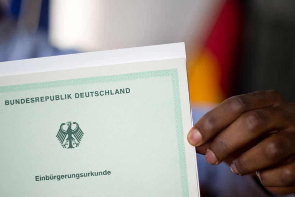 Ein Mann aus Afrika zeigt bei einer Einbürgerungsfeier stolz seine Einbürgerungsurkunde.