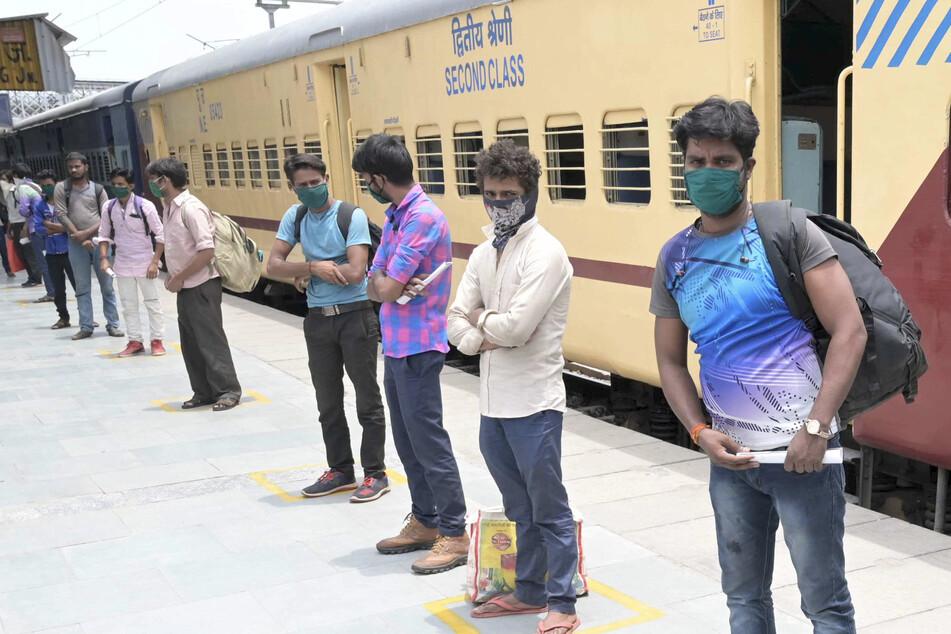 Migranten aus Kolhapur tragen Mundschutzmasken und warten in einer Warteschlange auf die Abfahrt mit Bussen in ihre Heimatdörfe. (Archivbild)