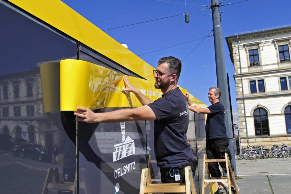 Die Werbetechniker Sebastian Findewirth (35) und Mario Pfeil (54) kleben die neuen Folien an ein Wartehäuschen.