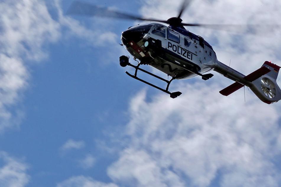 Mit Unterstützung durch einen Hubschrauber suchte die Polizei am Sonntagnachmittag nach den vier Insassen des verunglückten Renaults. (Symbolbild)