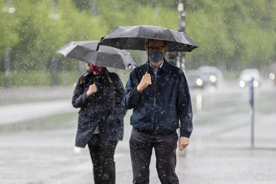 Ein Mann und eine Frau gehen bei starkem Regen mit Mund-Nasen-Schutz und Regenschirmen über den Platz des 18. März in Berlin.