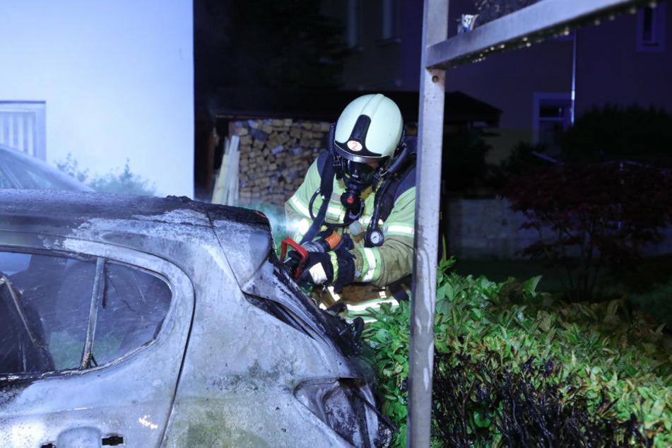 Hoch konzentriert löscht der Feuerwehrmann das Auto.