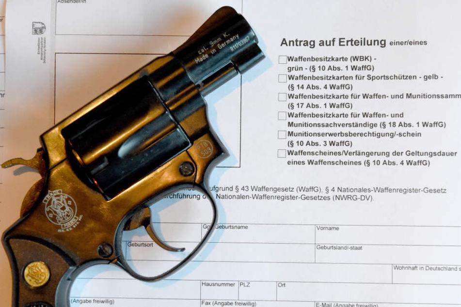 Ein Revolver liegt auf einem Antrag für die Ausstellung eines Waffenscheines.