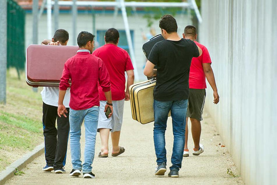 Geflüchtete laufen mit Koffern bepackt auf einem Weg einer Erstaufnahmeeinrichtung für Flüchtlinge in Ingelheim/Rhein.