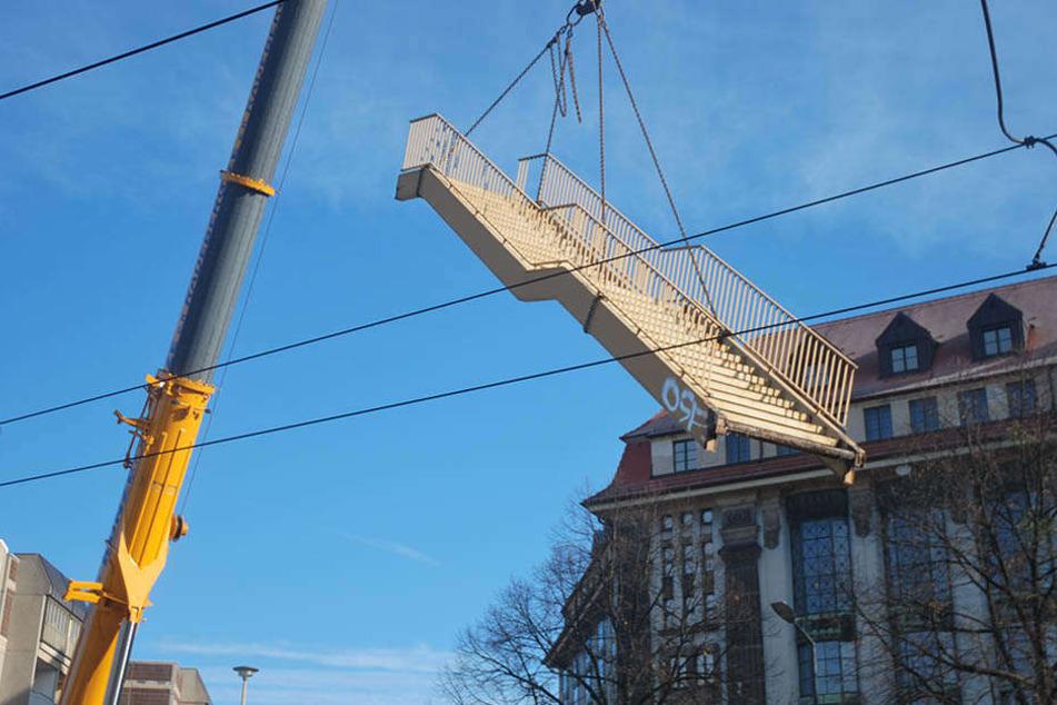 Mithilfe eines Krans wird die Brücke Stück für Stück abgetragen.