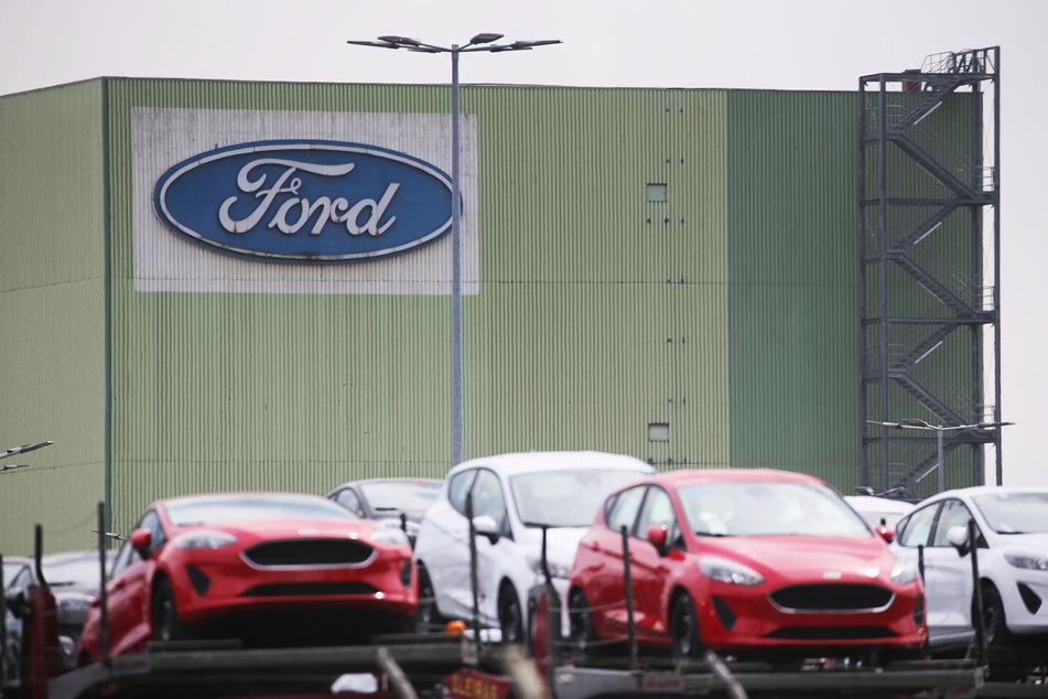Neu gebaute Autos stehen auf Lastwagen vor dem Ford Werk in Köln.
