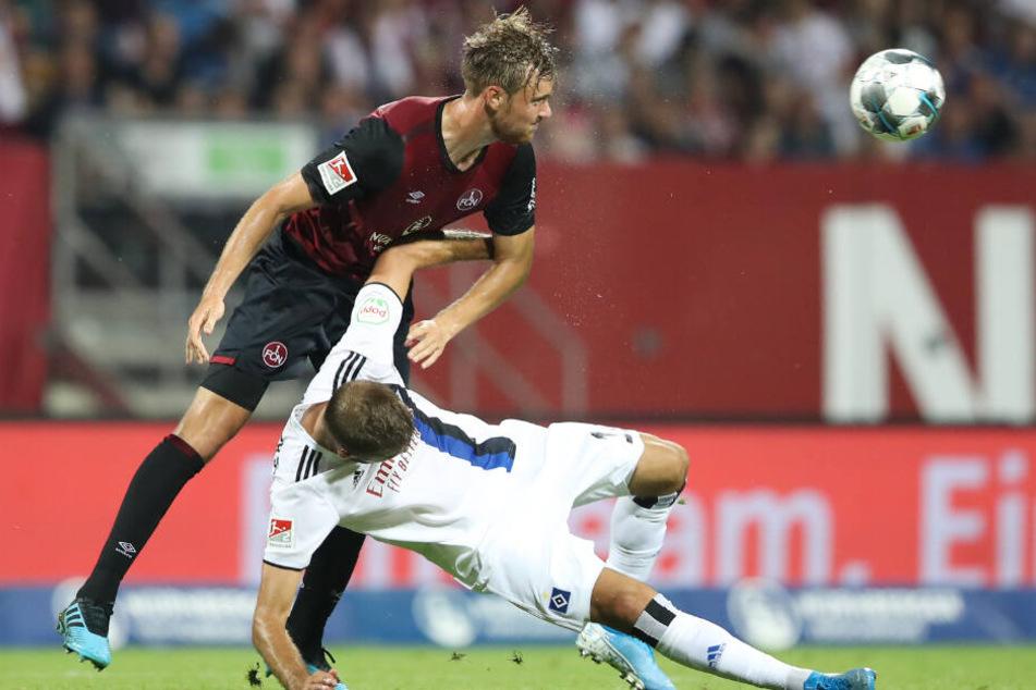 Stürmer Lukas Hinterseer wird bei einem Zweikampf mit Nürnbergs Ansgar Sörensen zu Boden gerammt.
