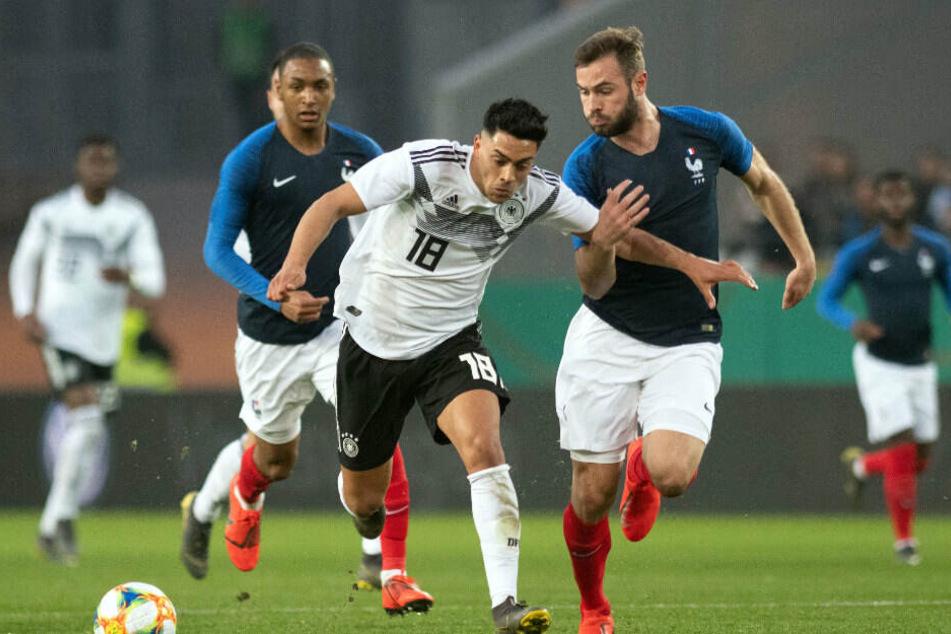 Deutschlands Nadiem Amiri (M) und Lucas Tousart (r) von Frankreich kämpfen um den Ball.
